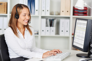 woman sitting at a computer with a headset on and smiling